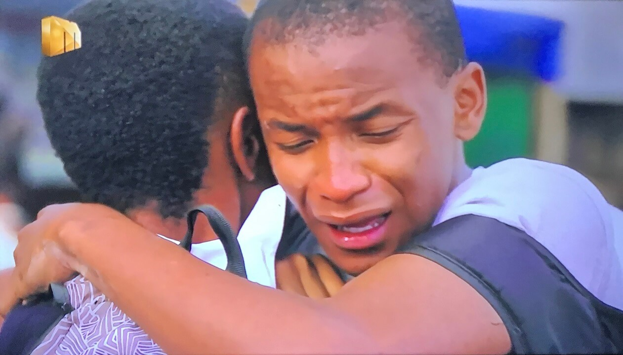 Teddy cries on Langa's shoulder